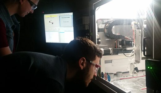 Researchers testing automated nanoparticle deposition procedures in an ultrasonic spray deposition system