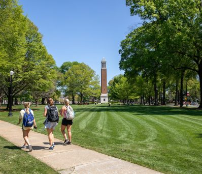 three students walking past the Denny Chimes tower